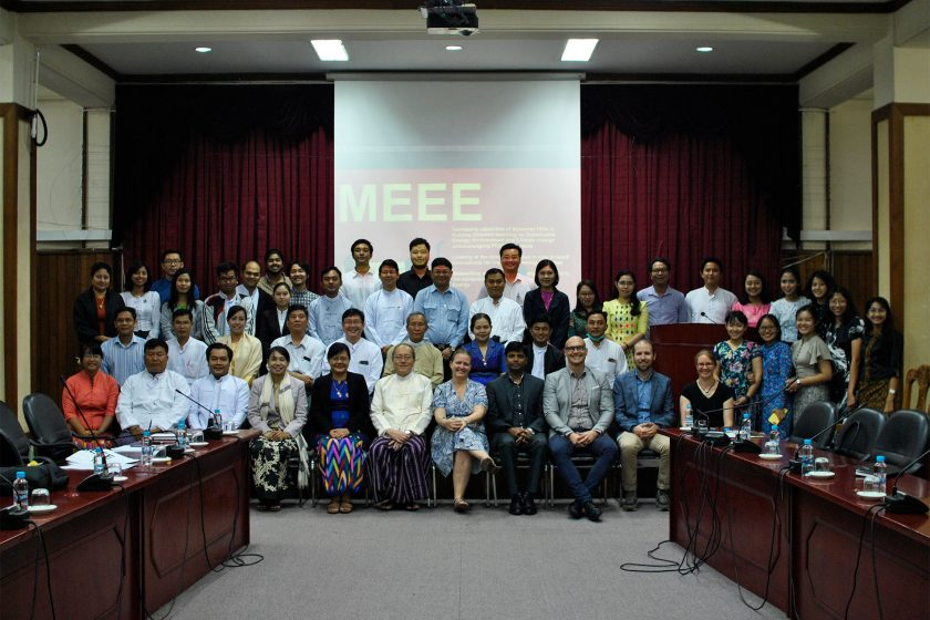 A group of smiling people posing in front of a projection screen with the letters MEEE in large writing.